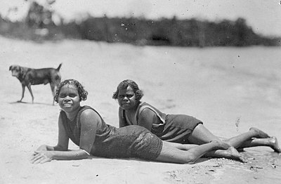 P15920 Two young girls in swimming costumes relaxing on Cairns Beach, 1927. Photographer S A Doblo