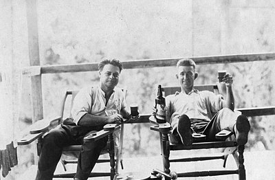 P15946 Stephen Doblo and friend relaxing on veranda in squatters chairs with record player and drinks, Christmas 1927