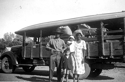 P17501 Young family about to board Green's bus at Forsayth c1955