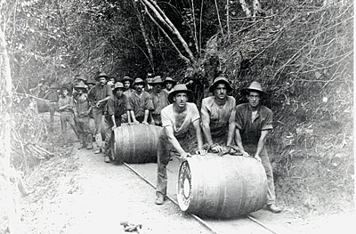 P02035 Workers rolling barrels of beer around hill no.10 tunnel, 1911. Cairns to Kuranda railway construction. Photographer: Alfred Atkinson